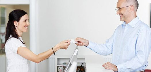 A man handing a woman a card over a service counter